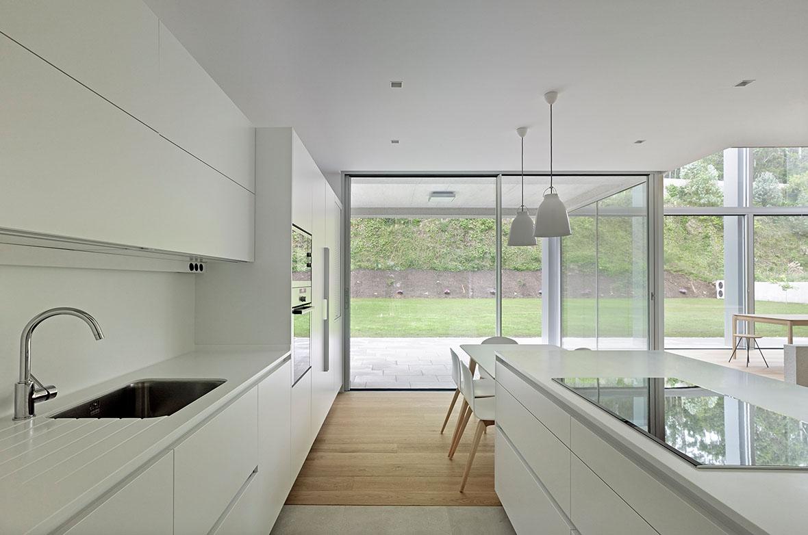 Cocina abierta blanca luminosa y con suelo contiguo Santos