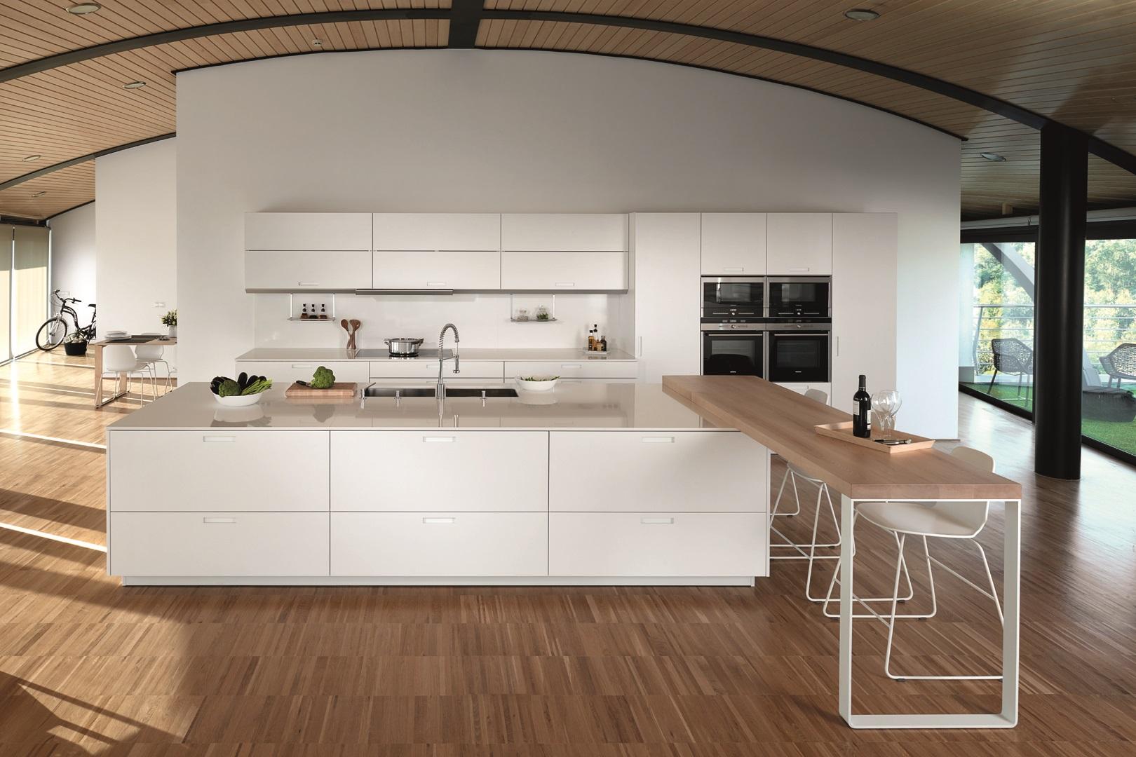Cocina blanca con barra y suelo de madera