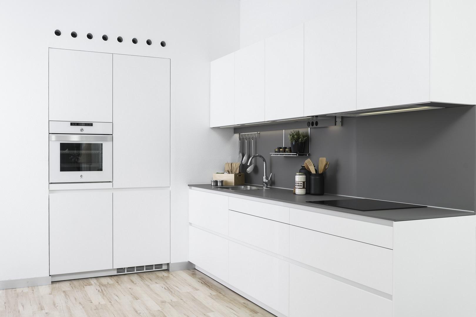 Cocina blanca con encimera y salpicadero gris
