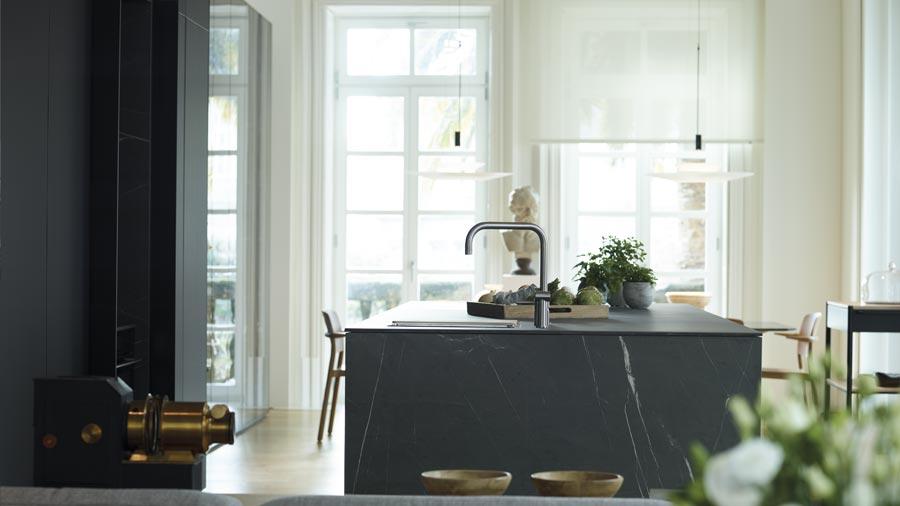 Cocina abierta con isla luminosa y muebles columna