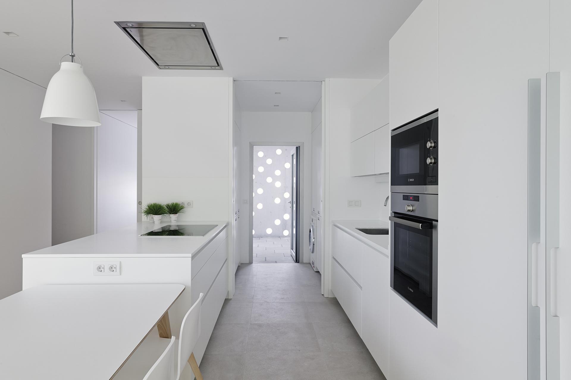 Cocinas-pequeñas-en-paralelo-con-barra-y-iluminación-Santos.jpg