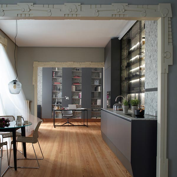 Cocina lineal con vitrina, abierta al estudio y al salón. Acceso