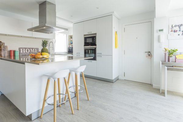 Una cocina blanca abierta al resto de la casa