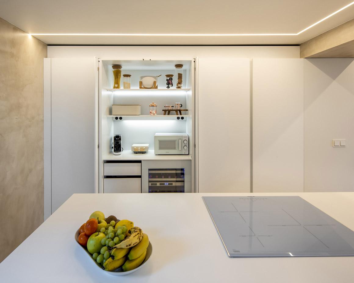 Cocina blanca con isla, armario escamoteable. Santiago Interiores