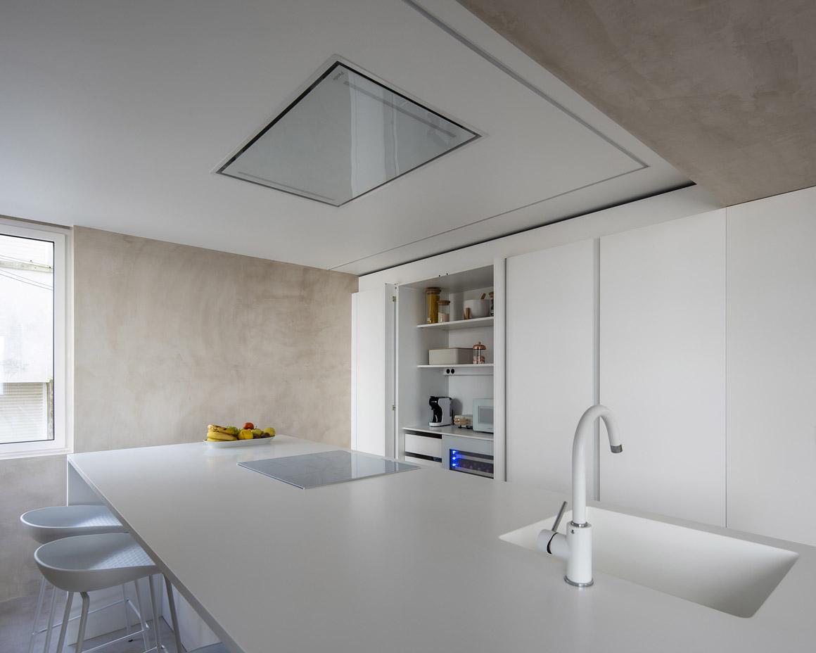 Cocina blanca con isla, armarios sin tirador. Santiago Interiores