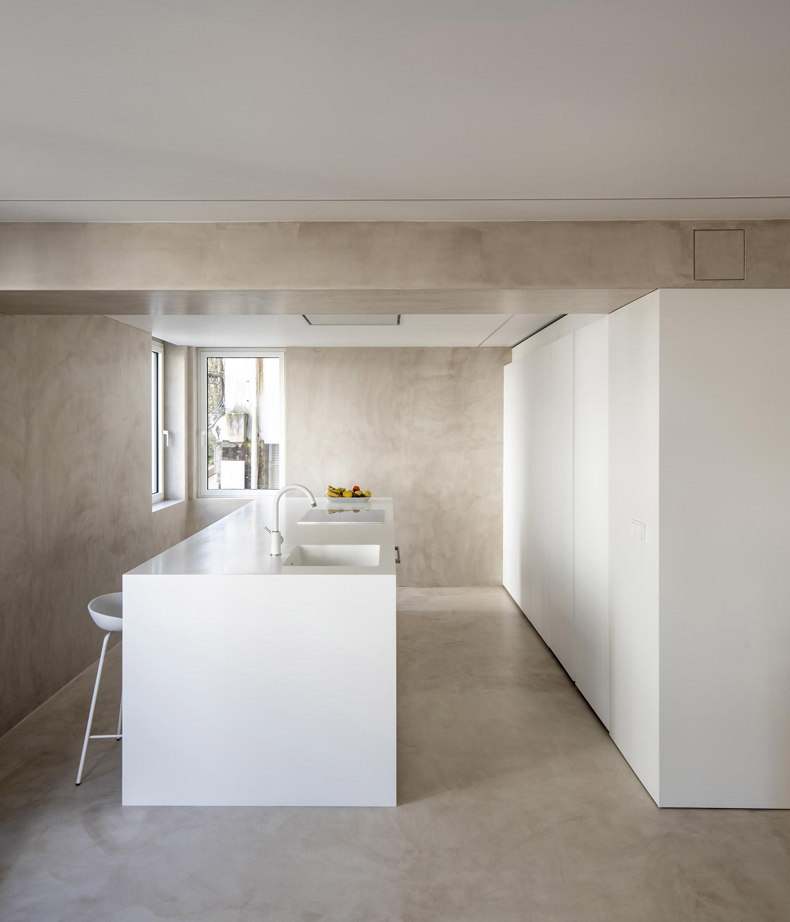 Cocina blanca con isla. Visión lateral. Santiago Interiores