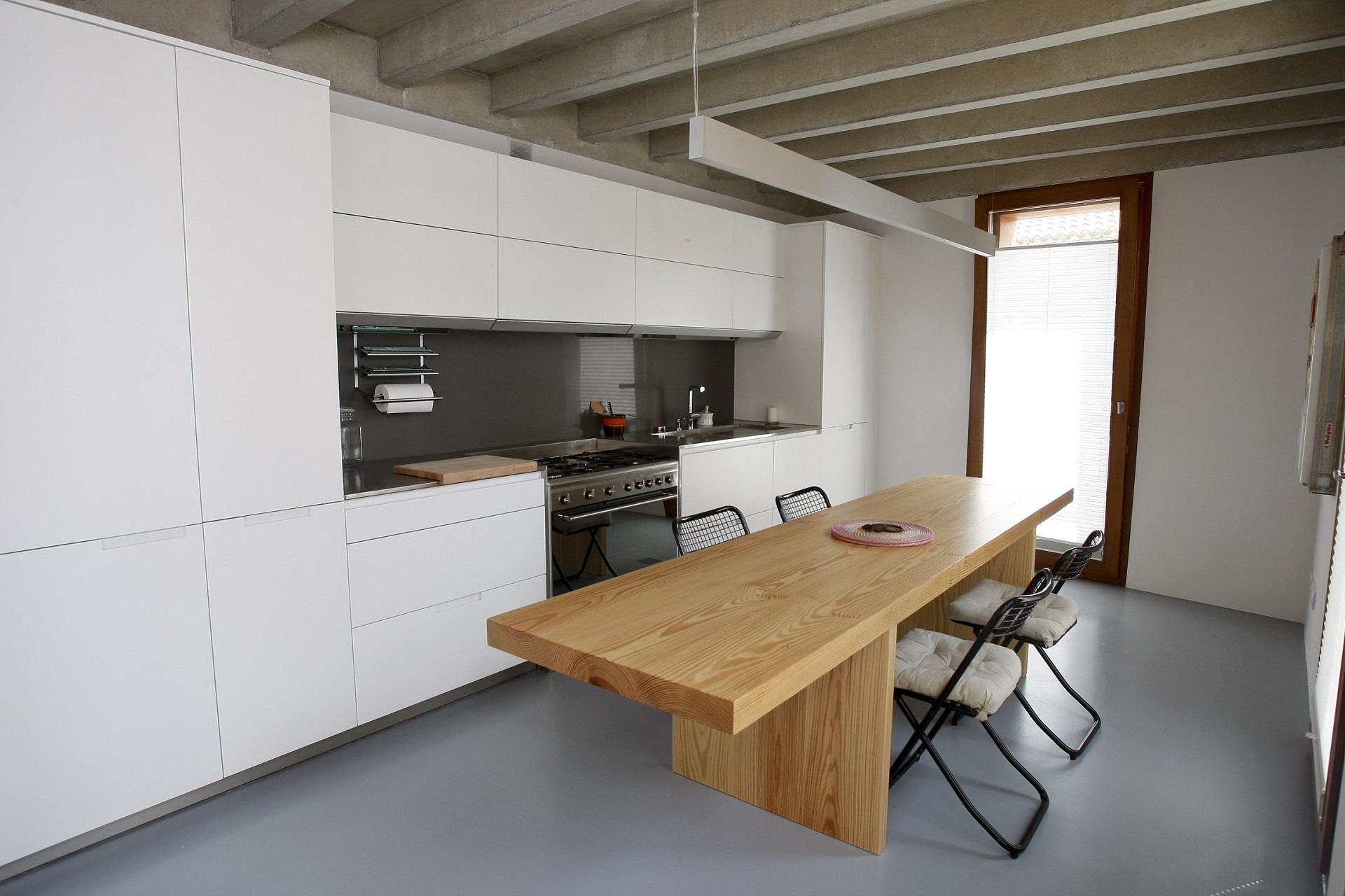 Cociña branca e gris con mesa de madeira Santos