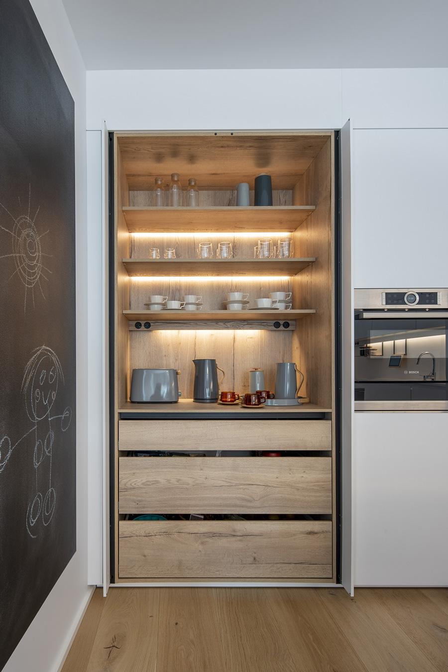 Pizarra en cocina abierta con estantería al fondo. Santiago Interiores