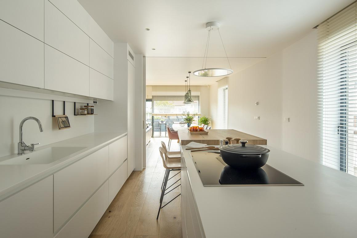 Vista perpendicular de cocina abierta blanca. Santos